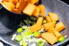 Pumpkin and leek cubes are cooked and sautéed in a non-stick pa stock image