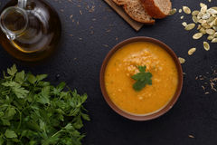 Pumpkin, lentil and carrot soup, bread and green on dark background Stock Photo