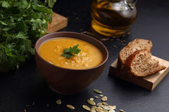 Pumpkin, lentil and carrot soup, bread and olive oil on the black table Royalty Free Stock Photos