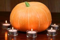 Pumpkin in light of candles. Orange pumpkin and tea light candles. Autumn halloween atmosphere Stock Image