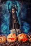 Pumpkin. Little girl in a costume of witch posing with pumpkins over dark background Royalty Free Stock Photo