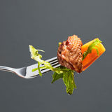 Pumpkin, meat and salad on a fork Stock Photos