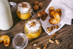 Pumpkin milkshake in glass jar with whipped cream, toffee, walnut and honey cookies. Bottle of milk. Dark wooden. Pumpkin milkshake with whipped cream, toffee stock photos