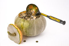Pumpkin with money. The pumpkin filled with metal coins with a wooden spoon royalty free stock photography