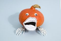 Pumpkin mouth skeleton. Composition of a pumpkin with skeleton hand wearing a paper drawn mouth and doll`s eyes on a pop vibrant blue background Royalty Free Stock Image