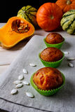 Pumpkin muffins in the green wrappers with squash seeds Royalty Free Stock Photos