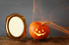 Pumpkin next to blank photo frame on wooden table Stock Photo