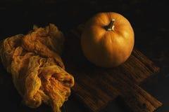 Pumpkin on old cutting Board , orange cloth ,dark background. Photo in low key Stock Photo
