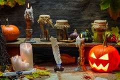 Pumpkin, old scrolls and candles in witch's cottage Stock Images
