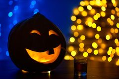 Pumpkin with one tooth decorated for Halloween party drinking juice. royalty free stock photo