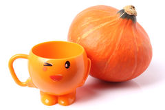Pumpkin and orange cup Royalty Free Stock Photos