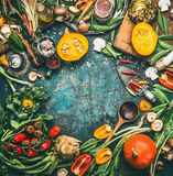 Pumpkin and Others organic harvest vegetables and ingredients with cooking spoon on rustic background, top view royalty free stock images