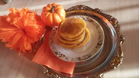 Pumpkin Pancake. With honey on a tin tray with the layout of pumpkins and a large orange flower and orange paper napkin Royalty Free Stock Image