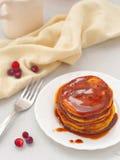 Pumpkin pancakes with caramel sauce and cranberries. Fresh homemade flapjacks. Top view Stock Photography