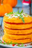 Pumpkin pancakes with chili pepper, parmesan cheese and rocket closeup. Pumpkin pancakes with chili pepper, parmesan cheese and arugula closeup on rustic stock photography
