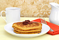 Pumpkin pancakes garnished with pecan halves. Royalty Free Stock Photography