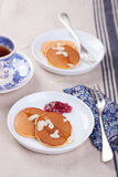 Pumpkin pancakes with honey, nuts and jam in a white plate on a table. Royalty Free Stock Photography