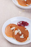 Pumpkin pancakes with honey, nuts and jam in a white plate on a table. Stock Photography