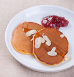 Pumpkin pancakes with honey, nuts and jam in a white plate on a table. Royalty Free Stock Image