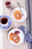 Pumpkin pancakes with honey, nuts and jam in a white plate on a table. Stock Photo