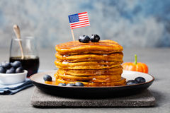 Pumpkin pancakes with maple syrup and blueberries on a plate with American flag on top Stock Photo