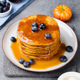 Pumpkin pancakes with maple syrup and blueberries on a plate. Grey stone background. Pumpkin pancakes with maple syrup and blueberries on a plate Grey stone Royalty Free Stock Photo