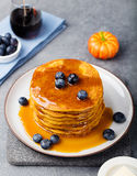 Pumpkin pancakes with maple syrup and blueberries on a plate. Grey stone background. Pumpkin pancakes with maple syrup and blueberries on a plate Grey stone stock image
