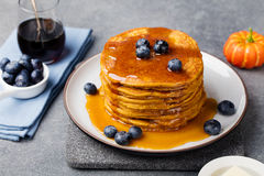 Pumpkin pancakes with maple syrup and blueberries on a plate. Grey stone background.  royalty free stock images