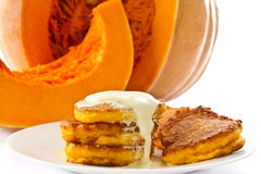 Pumpkin pancakes with sour cream. On a background of ripe pumpkins Royalty Free Stock Photo