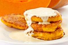Pumpkin pancakes with sour cream. On a background of ripe pumpkins Stock Photos