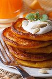 Pumpkin pancakes with sour cream close-up on the table. Stock Photo