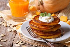 Pumpkin pancakes with sour cream and juice. With pulp closeup horizontal Royalty Free Stock Photo