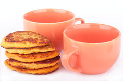 Pumpkin pancakes and two orange cups for breakfast Stock Images
