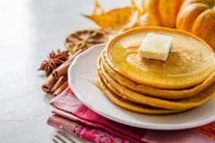 Pumpkin pancakes on white plate with butter and honey. White wood background Royalty Free Stock Photography