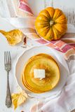 Pumpkin pancakes on white plate with butter and honey. White wood background Stock Image