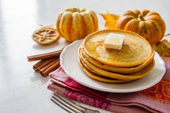 Pumpkin pancakes on white plate with butter and honey. White wood background Stock Photos