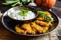 Pumpkin pancakes with zucchini and served with sour cream dip Stock Image