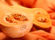 Pumpkin part. Ripe pumpkin part with seed on orange background Royalty Free Stock Photography