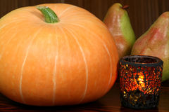 Pumpkin and pears. Pumpkin, pears and candle in stained glass. Autumn atmosphere Stock Photos
