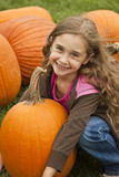 Pumpkin Picking. Little Girl Holding a big orange pumpkin in a patch with long blond hair Royalty Free Stock Photography