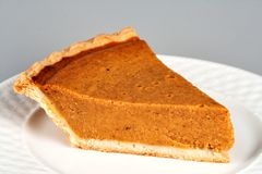 Pumpkin Pie. A slice of pumpkin pie served on a plate. This image can easily be isolated for insertion anywhere in your design royalty free stock image