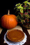Pumpkin Pie. A fresh pumpkin pie on display alongside a whole pumpkin and red and green foliage stock image