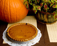Pumpkin Pie. A fresh pumpkin pie on display alongside a whole pumpkin and red and green foliage stock photo