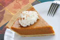 Pumpkin pie. With whipped cream served on white plate royalty free stock image