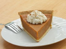 Pumpkin pie. Slice of pumpkin pie with whipped cream and sprinkled with cinnamon served on a white plate stock image