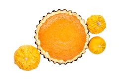 Pumpkin pie arranged with small pumpkins isolated on white backg Stock Photo