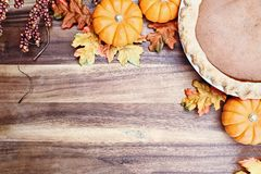 Pumpkin Pie and Autumn Leaves. Homemade pumpkin pie in pie plate with little pumpkins, autumn leaves and room for text over rustic wooden background. Image shot stock image