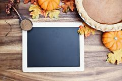 Pumpkin Pie and Blackboard. Homemade pumpkin pie in pie plate with little pumpkins, leaves, spice and blackboard with room for recipe or text over rustic wooden royalty free stock images