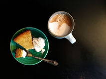 Pumpkin pie cheesecake with whipped cream and coffee on table. Top-down view of a piece of pumpkin pie cheesecake served with whipped cream on a green plate - a Stock Image