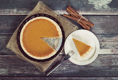 Pumpkin pie with cinnamon sticks on wooden table Royalty Free Stock Photos